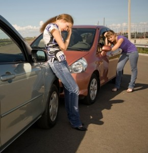 two females standing by car accident, driving and texting